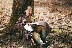 Young unidentified re-enactor dressed as Soviet soldier in overcoat resting Royalty Free Stock Photo