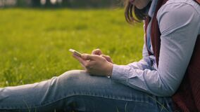 Woman Typing Text On A Smartphone Sitting On Lawn. Young Unidentified Woman In Casual Clothes Typing Text On A Smartphone Sitting On A Green Lawn In The Park On stock video footage
