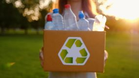 Young unidentified woman holds and hands a box with plastic bottles. Young unidentified woman holds in hands a box with plastic bottles with the icon of stock video footage