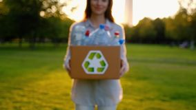 Young unidentified woman holds and hands a box with plastic bottles. Young unidentified woman holds in hands a box with plastic bottles with the icon of stock video