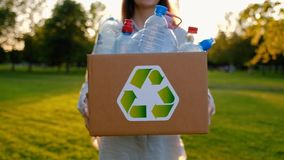 Young unidentified woman holds and hands a box with plastic bottles. Young unidentified woman holds in hands a box with plastic bottles with the icon of stock footage