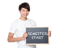 Young university student with blackboard showing phrase of semes Royalty Free Stock Photography