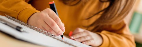 Young unrecognisable female college student in class, taking notes and using highlighter. Focused student in classroom. royalty free stock image