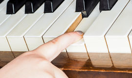 Young unrecognizable girl child, playing piano. By pressing down a key Stock Image