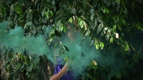 Young unrecognizable woman standing in foliage. And branches on background of big tree. Elegant girl in purple dress posing and dancing in green smoke stock video footage