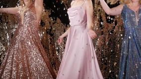 Girls throw sparkles. Young unrecognizable women in bright shiny dresses throw sparkles on a shiny gold background. Girls having fun in slow motion stock video