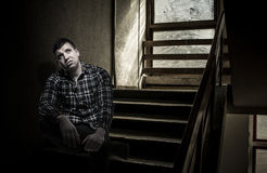 Young unsatisfied man sitting on stairs. Young upset brunette man wearing checked shirt sitting on stairs in public indoors looking up disgusted. Dwelling house Stock Images