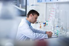 Young unshaken researcher sitting and working with his notebook. Laboratory records. Young cute unshaken researcher sitting in the laboratory concentrating on Stock Image