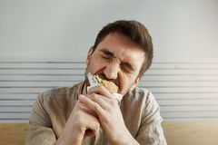 Young unshaven handsome guy with dark hair eating sandwich in fast food with closed eyes, with happy and satisfied Stock Photography