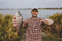 Fisherman. Young unshaven man in checkered shirt, cap and sunglasses caught a fish, shows it and points with a finger on it on the shore of lake on background of royalty free stock photo