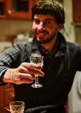 Young unshaven man holding glass of strong alcoholic drink looking ar camera. Cheers. Young unshaven man holding glass of strong alcoholic drink vodka looking ar Stock Photography