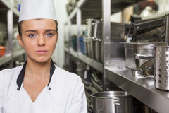 Young unsmiling chef standing arms crossed between shelves Stock Photography