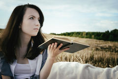 Young unusual girl illustrates conceptual idea with book Stock Photo