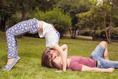 Young unusual kissing couple outdoors at park, in extreme position Stock Photo