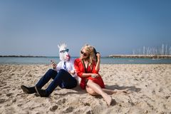 Young unusual man in funny mask is talking with girlfriend Royalty Free Stock Images