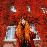 Young unusual pale girl with curly red hair on a autumn background. Beautiful redhead woman in a red coat and a green turban. Autumn bright look stock photo