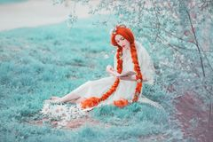 Young unusual redhead renaissance girl with curly hair braided in plait on a spring background. Beautiful woman with pale skin royalty free stock photos