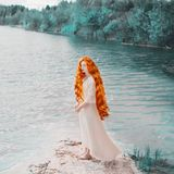 Young unusual woman with long hair, red lips, pale skin on blue water background. Beautiful redhead model against the lake. Unusual summer landscape stock images