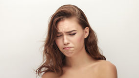 Young upset adorable brunette woman posing with closed eyes and bare shoulders on white studio background Royalty Free Stock Photography