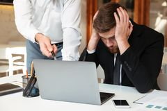 Young upset bearded businessman in black suit holding his head w. Hile his partner pointing with pen on laptop screen in office Royalty Free Stock Photo