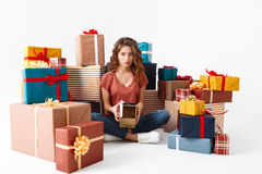 Young upset beautiful curly girl sitting on floor among gift boxes showing one she opened is empty  Royalty Free Stock Images
