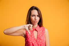 Young upset brunette woman showing thumb down gesture, looking a. T camera, isolated on yellow background Stock Photo