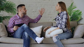 Young upset couple quarrel beacuse of man have internet addiction and his girlfrieng shout on him trying to take off stock footage