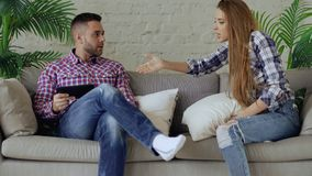 Young upset couple quarrel beacuse of man have internet addiction and his girlfrieng shout on him trying to take off stock image