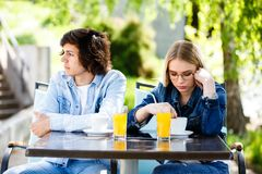 Young upset couple sitting side by side at cafe`s garden.  Royalty Free Stock Photography