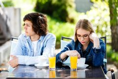 Young upset couple sitting side by side at cafe`s garden stock image