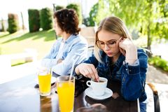 Young upset couple sitting side by side at cafe`s garden royalty free stock image