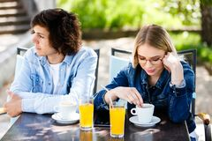 Young upset couple sitting side by side at cafe`s garden stock photos