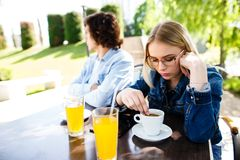 Young upset couple sitting side by side at cafe`s garden stock images
