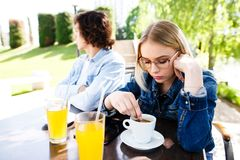 Young upset couple sitting side by side at cafe`s garden royalty free stock photo