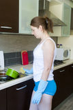 Young upset girl with gloves near sink Royalty Free Stock Image