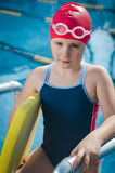 Young upset girl learning to swim in the pool Stock Photos