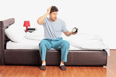 Young upset male sitting on a bed, holding a clock and gesturing stock photography