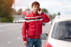 Young upset man calling to car assistance on road royalty free stock photography