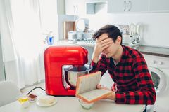 Young upset man reading complicated recipe in culinary book. Guy cooking pie with food processor on kitchen. Young upset man reading complicated recipe in stock photo