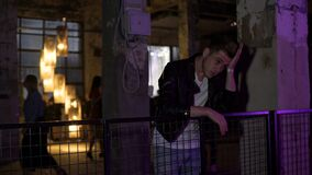 Young upset man thinking about problems while standing at nightclub hall. Stock footage stock footage