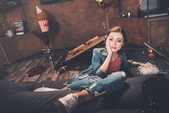 Young upset woman with hangover sitting on couch in messy room Stock Images