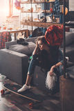 Young upset woman with hangover sitting on couch in messy room Royalty Free Stock Images