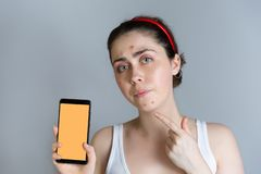 A young upset woman holding a smartphone and points her finger at the pimples on her face. The concept of cosmetology royalty free stock photos