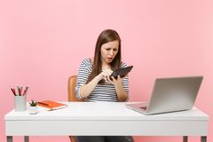 Young upset woman holding using calculator worried about troubles with calculations work at office with pc laptop. Isolated on pastel pink background stock photos