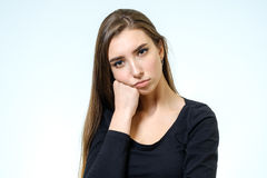 Young upset woman. Isolated on white background. Studio shot Royalty Free Stock Images