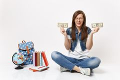 Young upset woman student crying holding dollar bills cash money have financial problem sit near globe, backpack school royalty free stock images