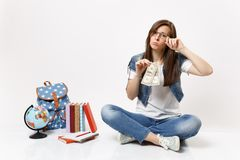 Young upset woman student crying holding dollar bills feeling stressed by lack of money sit near globe, backpack school stock photography