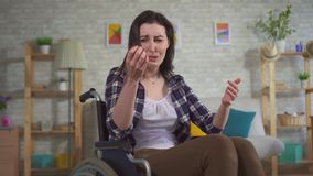 Young upset woman in a wheelchair a lot of hair falls out after chemotherapy stock video footage