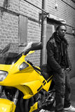 Young Urban African American Male Standing. Next to a Motorcycle Royalty Free Stock Image