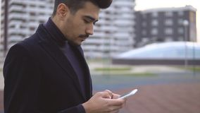 Young urban businessman professional in black suit walking in street using app texting sms message on smartphone.  stock footage
